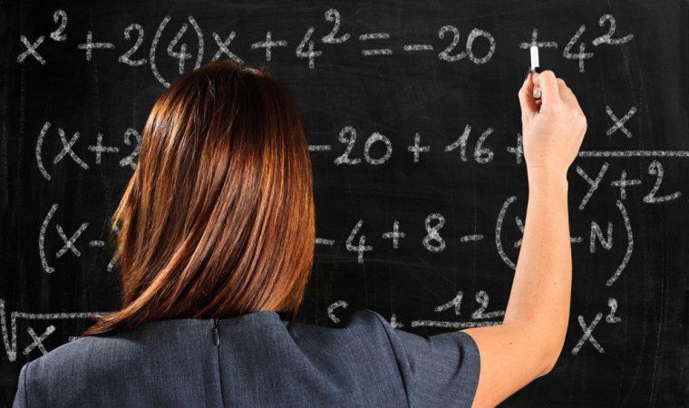 Professora de matemática resolve problema no quadro